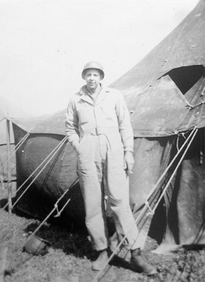 Photograph showing Corporal Jerome J. Lawrence posing in front of a Pyramidal Tent at the 11th Evacuation Hospital.Photo courtesy of David Lawrence.