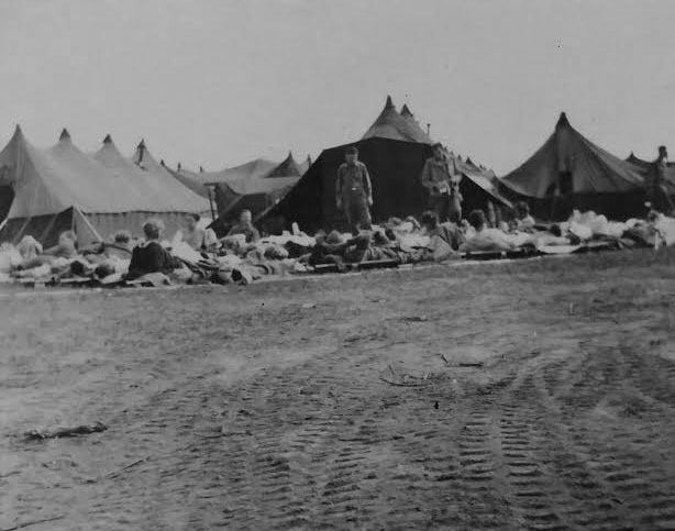 Partial view of bivouac of the 107th Evacuation Hospital following the capture of Brest, Brittany. A large number of German wounded PWs are grouped in front of the organization's tentage awaiting triage and admission. Photo taken some time around mid-September 1944.