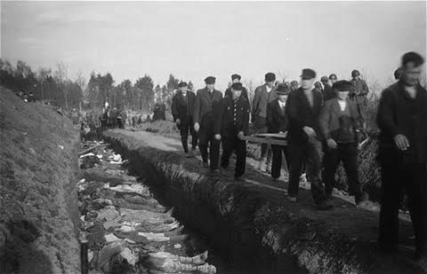 Vintage photo illustrating burial of Dora-Nordhausen Concentration Camp victims after the Camp's liberation 13-14 April 1945. German civilian and military authorities were compelled to help with recovery and burial operations and forced to pass by the mass graves to witness the horrible and tragic death of the many inmates by the Concentration Camp authorities. The 3d Hospitalization Unit, 51st Field Hospital, set up a temporary Surgical Hospital in the Camp between 12-17 April 1945 to help alleviate the suffering and offer treatment and care to the survivors.