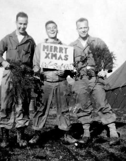 """Three members of the 107th Evacuation Hospital fooling around with a sign wishing everyone a """"Merry Christmas"""". Probably taken while the organization was billeted at the Collège Turenne, Sedan, France, from 22 December 1944 until 21 January 1945."""