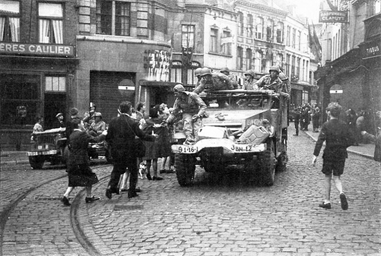 A 16th Infantry Regiment Halftrack and other vehicles from the 3d Battalion arrive in Mons, Belgium, in early September 1944.