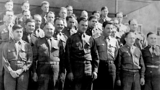 Picture illustrating Officers of the 107th Evacuation Hospital standing around their CO, Colonel H. W. Daine. Most probably taken around the end of the war in Würzburg, Germany.