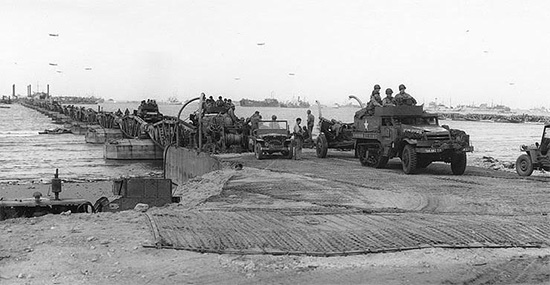 Picture illustrating one of the piers of the Omaha Beach Artificial Harbor taken some time around mid June 1944. The personnel of the 107th Evacuation Hospital landed at Omaha Beach, Normandy, France, on 12 July 1944.