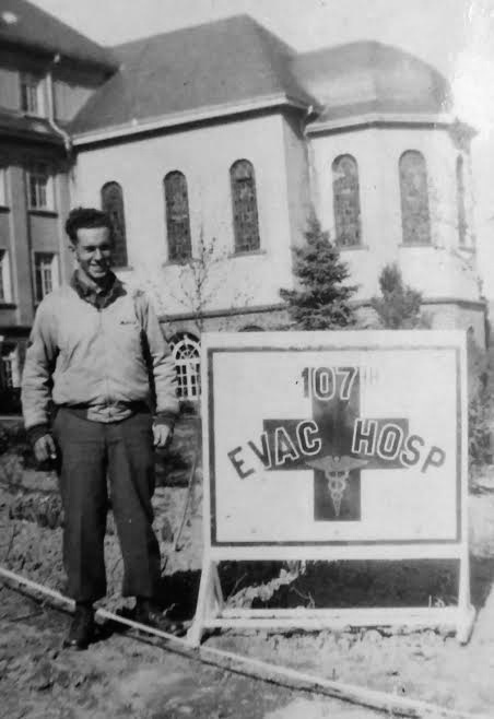 Picture illustrating Technician 5th Grade Robert W. Frisbie, with sign indicating the 107th Evacuation Hospital. Taken during the organization's stay at the Pensionnat St. Joseph, Hachy, Belgium, 21 January 1945.