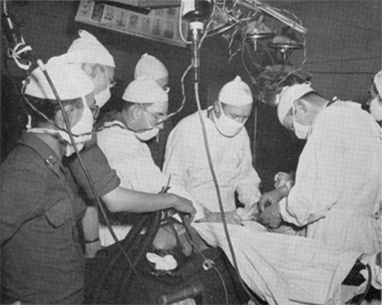 Photo illustrating an Operation Room with surgery going on, probably taken around mid-June 1944, following opening of the 51st Field Hospital in Normandy, France, on 11 & 12 June 1944.
