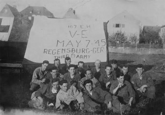 Group picture illustrating some members of the 107th Evacuation with a large sign indicating V-E Day. At the time the oganization was located under tentage outside of Regensburg, Germany. The Hospital remained in Regensburg from 30 April 1945 until 20 May 1945.