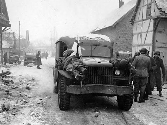 Winter scene. Recovered bodies of dead enemy soldiers are evacuated to the rear in American WC-54 3/4-ton ambulances. Photo taken 26 January 1945 in Germany.