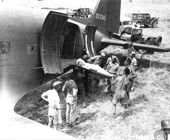 Another vintage photo illustrating a litter patient being carried aboard one of the C-47 aircraft, prior to his evacuation for further treatment in North Africa. Photo also taken at Agrigento, Sicily, 25 July 1943. The 802d MAETS was soon called in to provide medical attendants to accompany the casualties during flight.