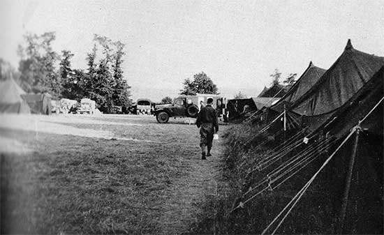 Partial view of the 34th Evacuation Hospital's set up near Carentan, France. Ambulance unloading casualties at the Receiving. Photo taken some time between 5 July and 6 August 1944.