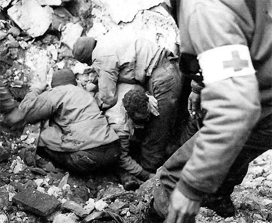 Vintage photo illustrating a GI buried in debris following an enemy bombing, being freed by medical personnel. Photo taken in Italy in January 1944.