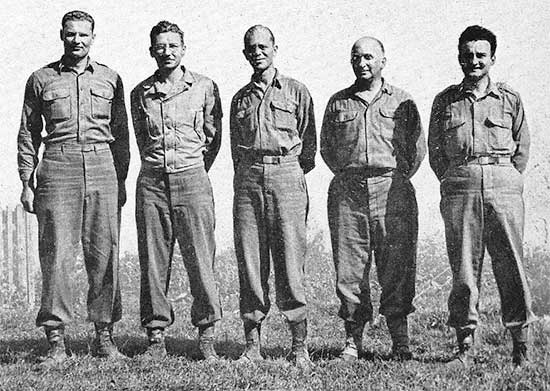 Photograph illustrating Headquarters Staff of the 34th Evacuation Hospital. From L to R: First Lieutenant Daniel B. Kohn; Enlisted Men Lawrence Bruemmer;  Robert A. Fletcher; and Captain Seymour Katzenstein.