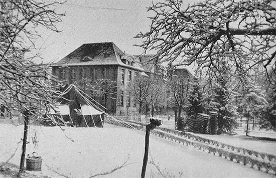 Front view of the 34th Evacuation Hospital at Metz, France. The organization took over buildings formerly occupied by the Wehrmacht and used as a military hospital during their occupation of France. Photograph taken in the winter of 1944-45.