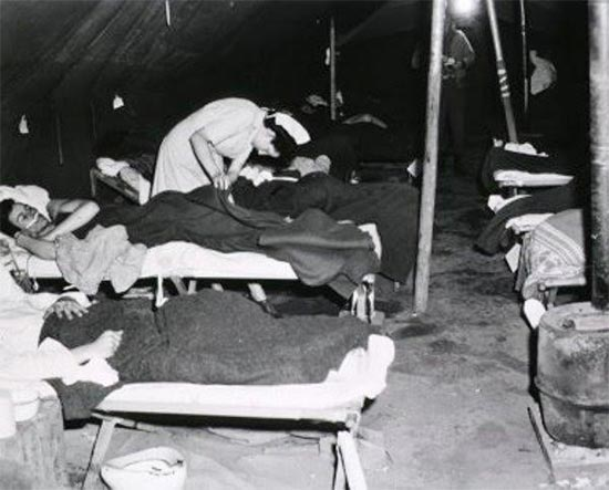 Vintage photo illustrating a Nurse at work in a Ward Tent. Photo taken March A944, at Bucciano, Italy, where the entire 11th Field Hospital was established between 9 and 11 March 1944.