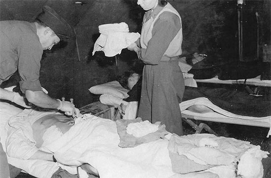 Vintage photo illustrating medical personnel pertaining to Unit I, 11th Field Hospital, at work. Photo taken early October 1944 in Alsace, France.