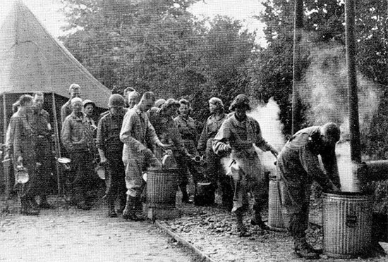 Daily scene taken at La Haye-du-Puits, Normandy, France. After enjoying chow, male and female personnel wash, rinse and clean their mess kits in the corresponding immersion containers. Picture taken some time during September 1944.