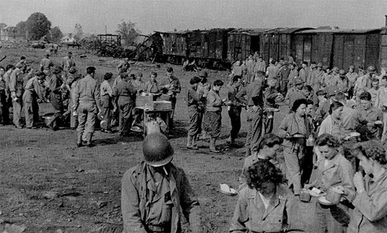 Picture of 58th General Hospital personnel enjoying some food, during a stop while traveling to La-Haye-du-Puits, Normandy. A partially destroyed train is visible in the background.