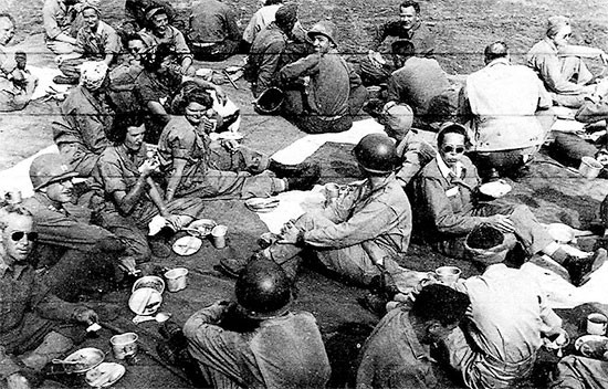 June 1-6, 1944. Picture of 56th Evacuation Hospital personnel having chow on the ground, while stationed at Fondi, Italy.