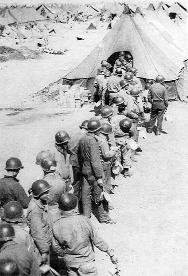 Picture illustrating the 56th Evacuation Hospital chow line for Enlisted Men. Wearing steel helmets eventually became compulsory because of the constant bombing and shelling by enemy long-range artillery and aircraft.