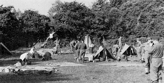Partial view illustrating personnel of the 58th General Hospital pitching their individual tents at Osmanville, Normandy, where they joined the 7th Field Hospital which served as a reception and concentration center for medical personnel arriving in Normandy. The organization would only spent a short period of time in this location (July 31 – August 2, 1944).