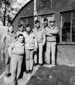 Group picture illustrating Quentin C. Unruh and friends in front of their Quonset hut, Stowell Park, England. Front row: Quentin C. Unruh; back row, from L to R: Holland C. Swallow, Paul E. Jones, unknown, James H. Day, Jesse Pitts, and Thomas J. Pollock.
