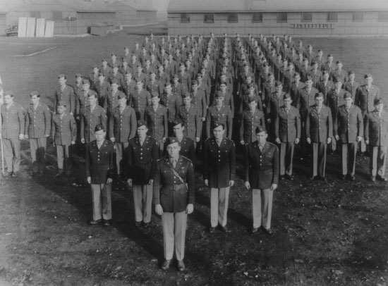 Photograph showing personnel of the 603d Quartermaster Graves Registration Company at Fort Lewis, Washington, 23 December 1943. The Service Club is in the left background, while barracks buildings are behind the men.