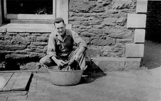 Photo illustrating Technician 5th Grade Stephen M. Benton, Fourth Platoon, 607th QM GR Co, washing some clothes, while being stationed at Camp Knowle, Bristol, England